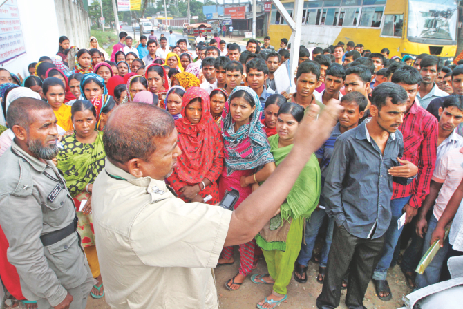 Following rumours of vacancies, a large number of garment workers throng the Sharmin Group factory at Ashulia on the outskirts of the capital yesterday asking for jobs. A security man at the gate is seen telling them to go away since there were no jobs there. Photo: Palash Khan