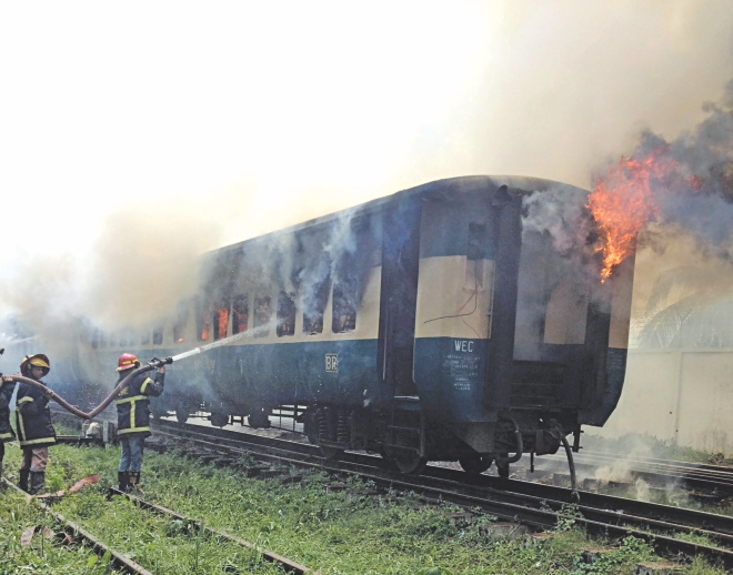Firefighters try to control the blaze in Kalni Express, a train heading for Dhaka from Sylhet, at Cantonment Railway Station in the capital yesterday. Photo: Courtesy