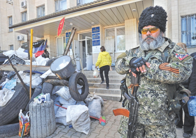 A pro-Russian militant holds a Kalashnikov as he guards a barricade outside the city hall in downtown Kramatorsk, eastern Ukraine, yesterday, a day after heavy fighting between pro-Russian militants and Ukrainian troops killed at least 34 people near the eastern Ukrainian city of Slavyansk. Photo: AFP