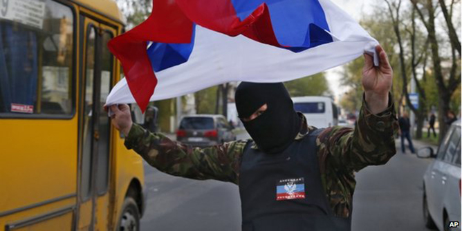 A masked pro-Russia protester waves the Russian flag in Donetsk, eastern Ukraine, on 22 April 2014 Moscow denies being behind the protests and seizures of buildings by pro-Russia militants