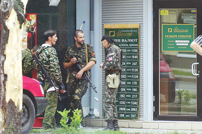 Pro-Russian insurgents guard a bank in the eastern Ukrainian city of Donetsk yesterday. Retreating pro-Russian insurgents dug in yesterday in Ukraine's sprawling industrial hub of Donetsk after government forces scored a string of morale-boosting victories in the bloody battle for the future of the country. Photo: AFP