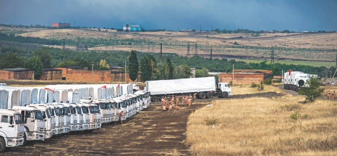 Lorries, part of a Russian humanitarian convoy, are parked not far from a checkpoint at the Ukrainian border some 30 km outside the town of Kamensk-Shakhtinsky in the Rostov region, yesterday. Tension between Moscow and Kiev is simmering over Russia's decision to try and deliver what it claims to be a huge humanitarian aid convoy that the Ukrainian authorities fear may be used to smuggle in arms to the pro-Kremlin insurgents. Photo: AFP