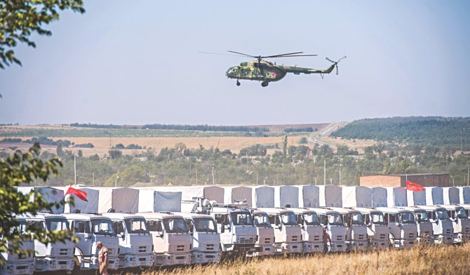 A Russian military helicopter flies over the trucks of Russian humanitarian convoy near Russian-Ukrainian border yesterday.  Photo: AFP