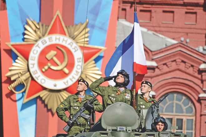Russian soldiers salute Vladimir Putin and Prime Minister Dmitry Medvedev during a Victory Day parade at the Red Square in Moscow, yesterday.  Photo: AFP