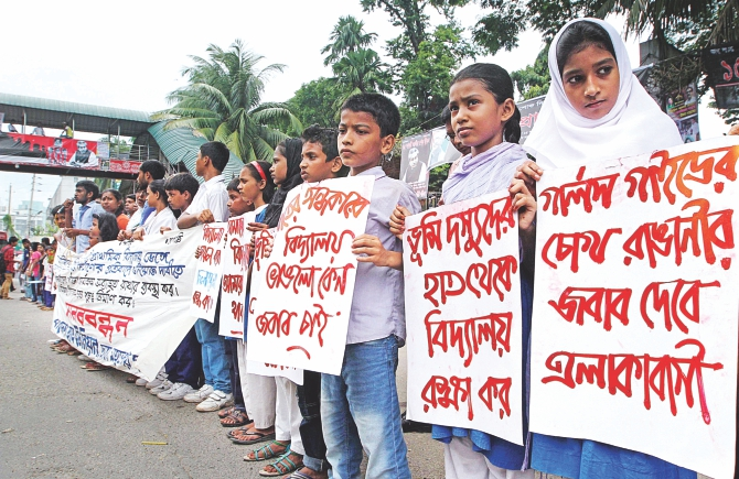 Students of Samajik Shikkhakendra Government Primary School on the capital's Bailey Road form a human chain before Jatiya Press Club yesterday protesting demolition of the school by Bangladesh Girl Guides Association during the Eid-ul-Fitr vacation. Photo: Palash Khan