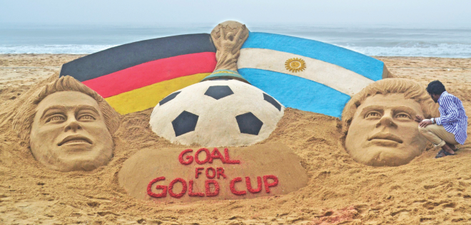 Indian sand artist Sudarshan Pattnaik works on a sand sculpture depicting the World Cup trophy along with Germany captain Philipp Lahm (L) and Argentina captain Lionel Messi on a beach at Puri in the eastern state of Odisha on Saturday. PHOTO: REUTERS