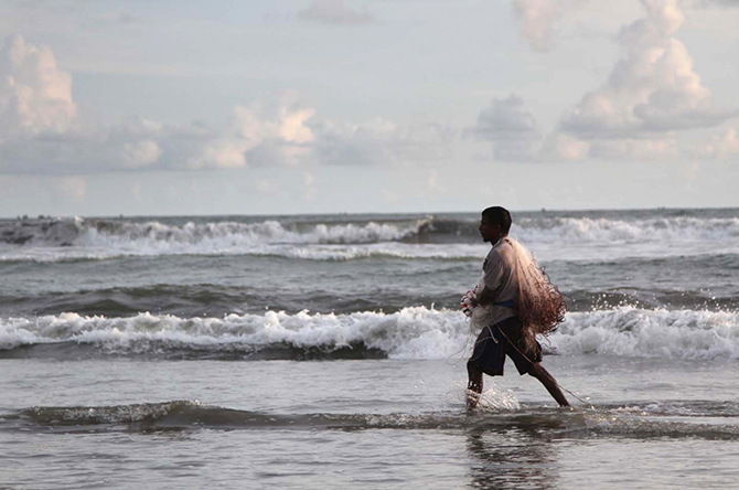 This Star photo taken on July 14, 2014 shows a fisherman on his way to work at Cox's Bazar sea beach in Chittagong.