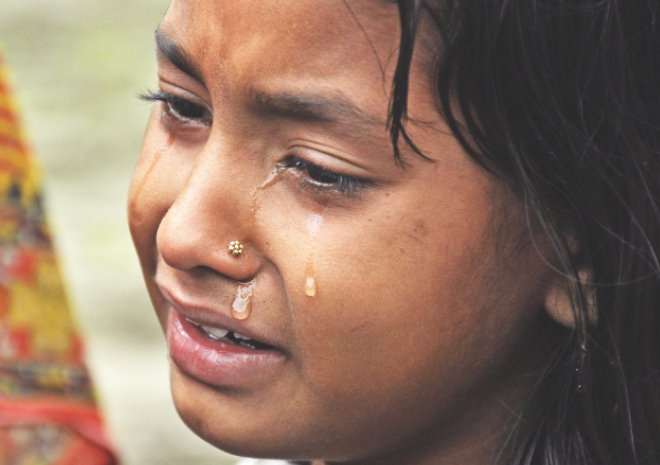 A young Indian child mourns after the death of a relative in Assam yesterday. Photo: AFP