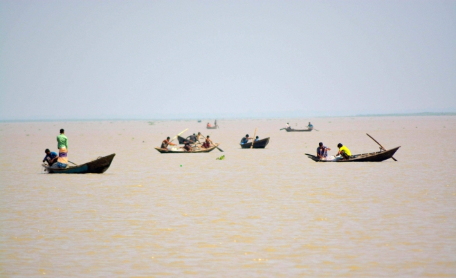 Although the ongoing peak season sees serious crisis of hilsa in the southern region, hard-pressed fishermen on small boats continue efforts to catch the popular fish. The photo was taken from Tentulia River in Baufal upazila under Patuakhali district yesterday.  PHOTO: STAR
