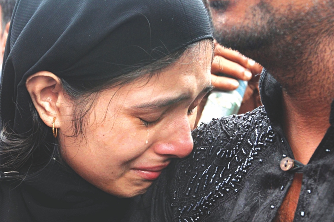Labony Akhter shedding tears on her uncle Shahidul Islam's shoulder at Mawa ferry terminal yesterday. She lost three members of her family -- her sister Rozina Akhter, aunt Ayesha Akhter, and cousin Sara Islam -- when Pinak-6 went down. The uncle in the picture had managed to swim ashore. Photo: Anisur Rahman