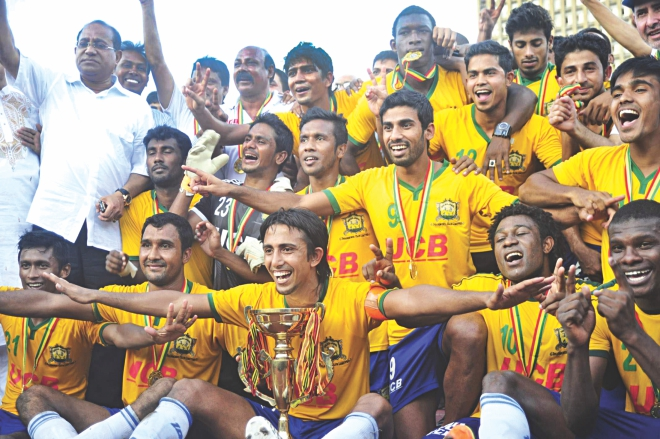 Players and officials of Sheikh Jamal Dhanmondi Club celebrate with the trophy after becoming Bangladesh Premier League champions with two matches in hand at the Bangabandhu National Stadium yesterday. PHOTO: STAR