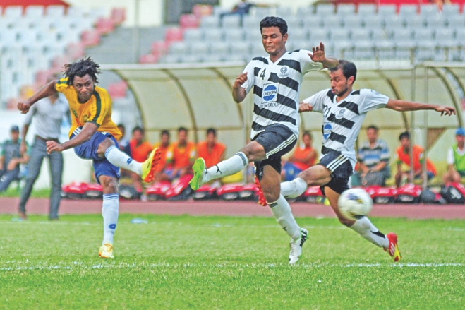Sheikh Jamal's Haitian hitman Sony Norde rockets the ball past Mohammedan defenders to score the first goal against the black and whites in their Bangladesh Premier League match at the Bangabandhu National Stadium yesterday. PHOTO: STAR
