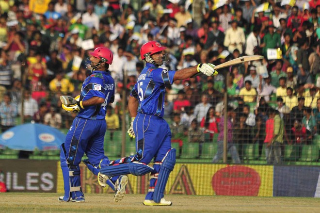 PARTNERS IN HISTORY: Afghanistan's Samiullah Shenwari (R) salutes the crowd on reaching his half-century while he and Asghar Stanikzai, who also hit a half-century, run a single to lift their side against Bangladesh in the Asia Cup at the Fatullah Cricket Stadium in Narayanganj yesterday. PHOTO: STAR