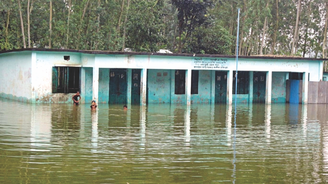 Shimulbari Government Primary School in Dhunat upazila of Bogra has been declared closed as it is partially submerged in water after the river Jamuna flooded, leaving the fates of the students' education uncertain. Photo: Star