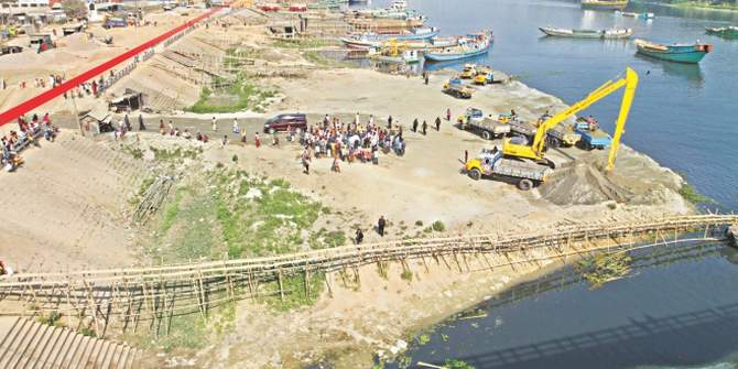 In this Star file photo, a digger at Kanchpur bridge on the Shitalakkhya river is seen evicting sand traders who occupied the river way beyond the walkway, marked in red, built on the bank.