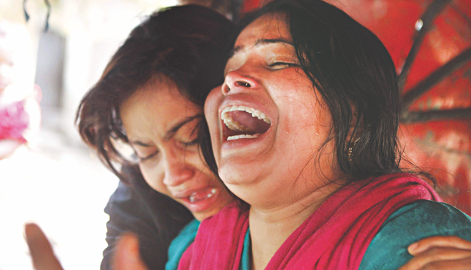 "Wife and daughter of Sangram, who was killed in a ""crossfire"" involving Rab, crying inside a three-wheeler in front of Mitford Hospital in the capital yesterday.  Photo: Rashed Shumon"