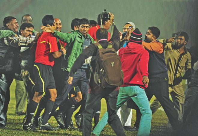 The referee is being escorted to safety by police as a mob charged the official at the end of the feisty encounter. PHOTOS: STAR