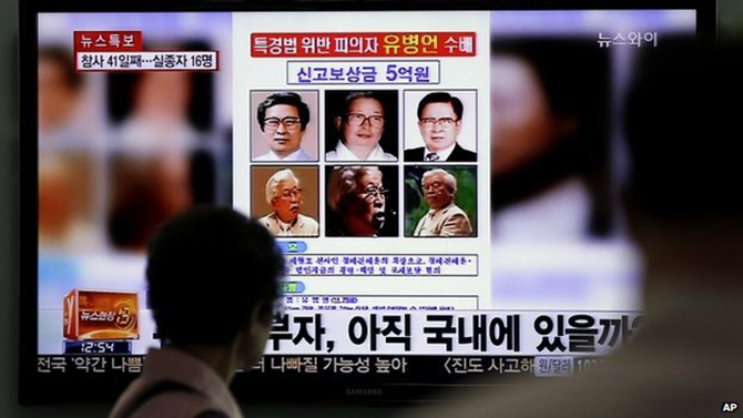 A woman looks at a 'wanted' poster for Yoo Byung-eun, shown on a South Korean TV news channel - 26 May 2014 A nationwide manhunt for ferry company owner Yoo Byung-eun was launched after the disaster