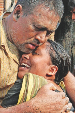 A woman cries her heart out being embraced by her husband after losing literally everything in a fire that swept through a slum area at Jhilpar in the capital's Madhubagh yesterday.  Photo: Anisur Rahman