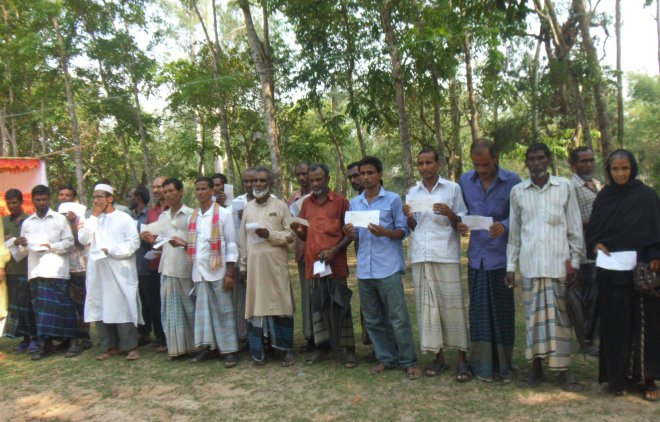 People serving as caretakers of plantations under the government's social afforestation programme in Bashtoil Range of Mirzapur upazila under Tangail district pose for photograph with the cheques they received as benefit for the work at a programme last week. PHOTO: STAR