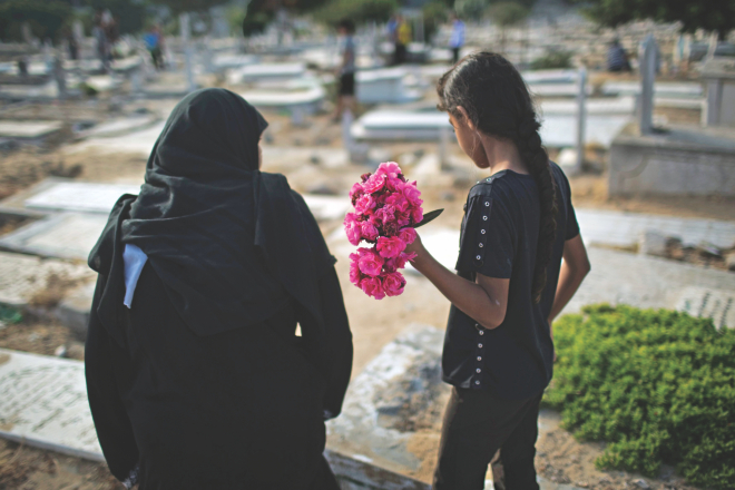 A Palestinian woman and a girl carry flowers to a family grave on Eid at a cemetery in Gaza City on Monday. Photo: Reuters