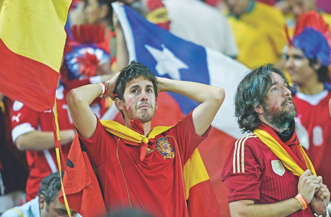 Disconsolate Spanish fans reflect after their team relinquished the World Cup with a 2-0 defeat to Chile in a Group B match at the Maracana Stadium in Rio de Janeiro on Wednesday. PHOTO: AFP