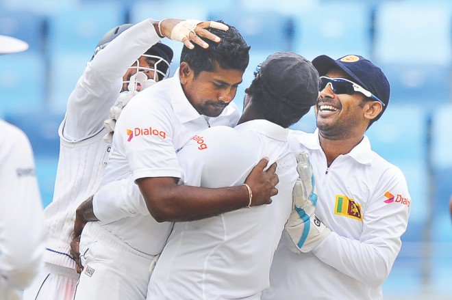 Sri Lanka captain Angelo Mathews lifts spin bowler Rangana Herath after the latter got rid of Pakistan skipper Misbahul Haq in Dubai yesterday. PHOTO: AFP
