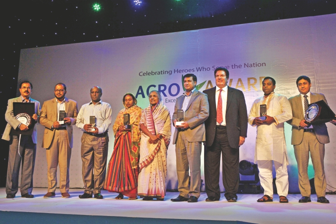 Fifth from left, Matia Chowdhury, agriculture minister, and Jim McCabe, chief executive officer of Standard Chartered Bangladesh, pose with the winners of the first AGROW Award from Standard Chartered at a ceremony at Sonargaon Hotel in Dhaka yesterday. Photo: Star
