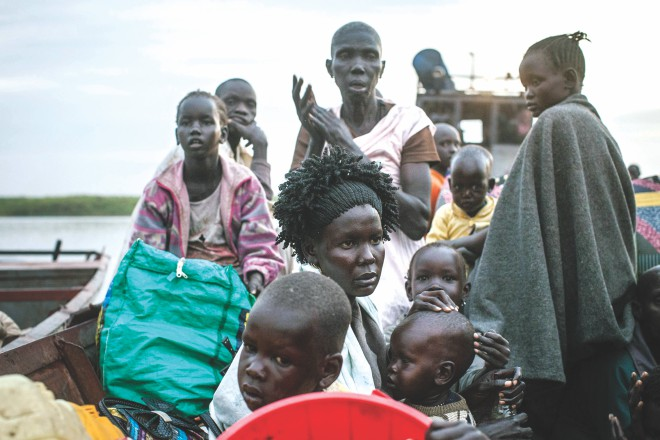 "People arrive at Minkammen, a small South Sudan port yesterday, fleeing violence in Bor region. South Sudan's young democracy risks ""shattering"" amid fierce fighting which has cost over 1,000 lives, a top US official warned yesterday. Photo: AFP"