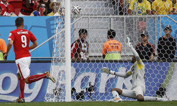 Switzerland's forward Haris Seferovic (L) scores past Ecuador's goalkeeper Alexander Dominguez during a Group E football match between Switzerland and Ecuador at the Mane Garrincha National Stadium in Brasilia during the 2014 FIFA World Cup on June 15, 2014. Photo: AFP/Getty Images