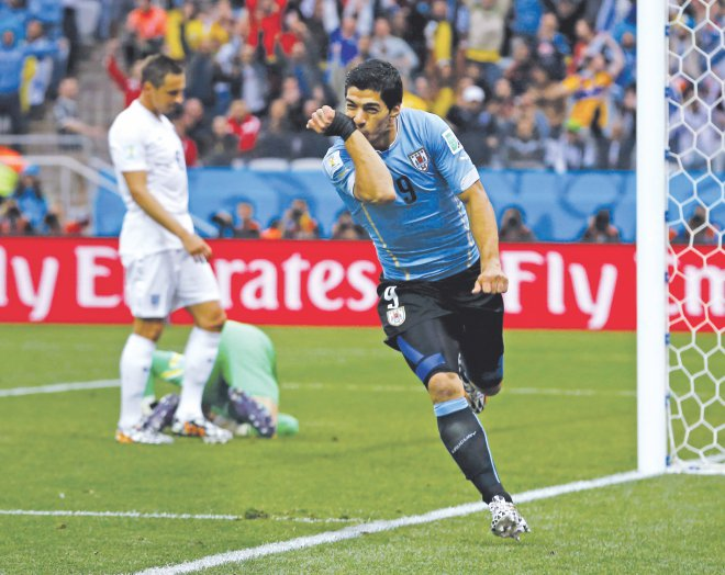 Uruguay's talismanic forward Luis Suarez celebrates his opening goal against England during their World Cup Group D match at the Corinthians Arena in Sao Paulo yesterday. Suarez later scored another one as Uruguay won 2-1. PHOTO: AFP
