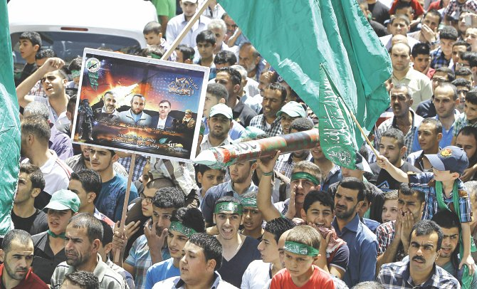 Supporters of the Palestinian Islamist Hamas movement gather during a demonstration in the West Bank city of Nablus to support people in the Gaza Strip yesterday. Five Palestinians were killed in new Israeli air strikes on Gaza yesterday, raising the death toll since July 8 to 2,087 Palestinians dead and 67 Israelis.  Photo: AFP