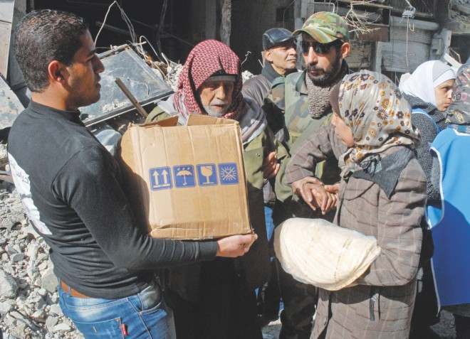 Residents of Syria's besieged Yarmuk Palestinian refugee camp, south of Damascus, receive UN food parcels yesterday. A food convoy gained entry to the Yarmuk refugee camp, where dozens have died from shortages of food and medicines, the UN and Syrian state media said. Photo: AFP