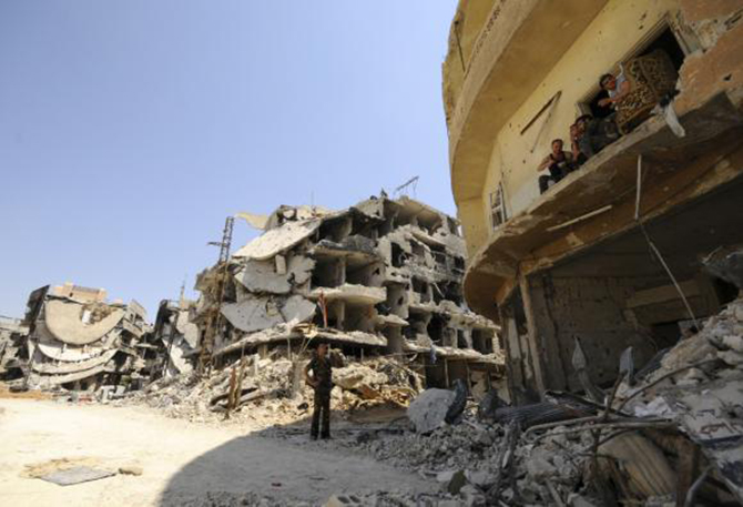 A Syrian army soldier loyal to Syria's President Bashar al-Assad chats with fellow fighters sitting on a balcony of a damaged building in Mleiha, which lies on the edge of the eastern Ghouta region near Damascus airport, after taking control of the area from rebel fighters August 15, 2014. Photo: Reuters