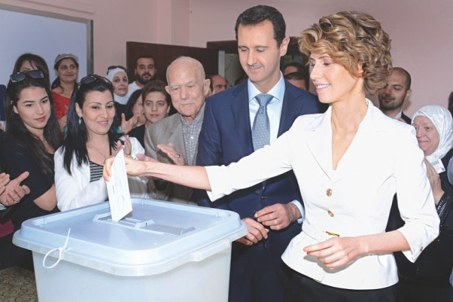 Syrian President Bashar al-Assad (C) watching on as his wife Asma casts her vote at a polling station in central Damascus.  Photo: AFP