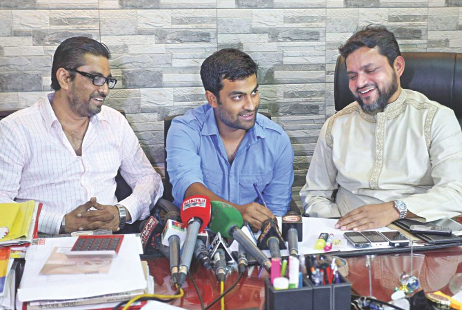 Opening batsman Tamim Iqbal signs for Gazi Tank Cricketers for the upcoming Dhaka Premier League as club owner Lutfur Rahman Badal (R) watches yesterday. The club has also bagged Shakib Al Hasan, who is expected to play in the competition in October. PHOTO: STAR