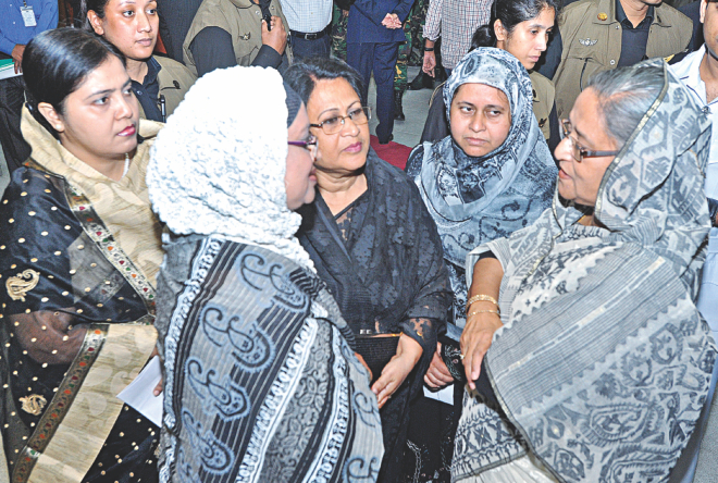 Prime Minister Sheikh Hasina talks with family members of the army officers, killed in the 2009 BDR massacre, after handing them over cheques as financial assistance from Bangladesh Association of Banks at her office yesterday. The assistance is given annually in cooperation with the Prime Minister's Office.  Photo: BSS
