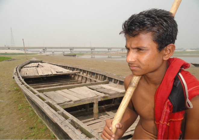 A boatman gives a despaired look as his boat lies idle due to emergence of large chars in the Teesta River that sees scanty flow amid unilateral withdrawal of water in the upstream by India, coupled with lack of rain during the ongoing summer. The photo was taken from near the Teesta Bridge in Lalmonirhat district a couple of days ago. PHOTO: STAR