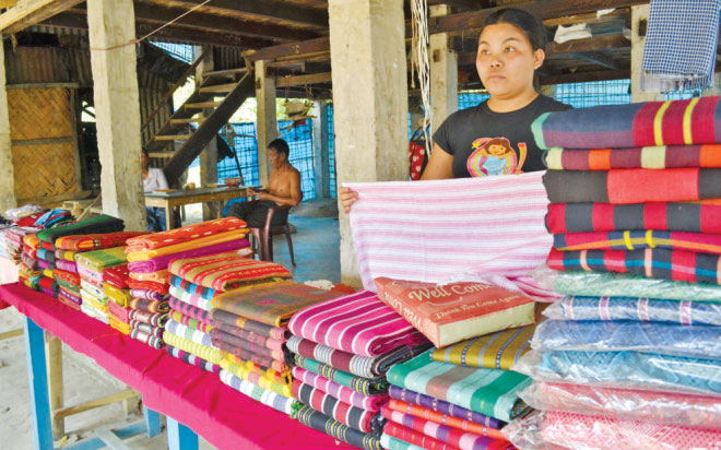A Rakhaine woman sells clothes at her shop in Misripara.