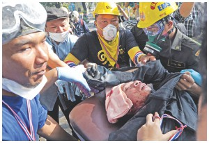 An injured is being taken to a hospital after clashes with police. Thai police fired tear gas as violent clashes broke out with opposition protesters who stormed a sports stadium in the capital to try to prevent political parties registering for elections. Photo: AFP