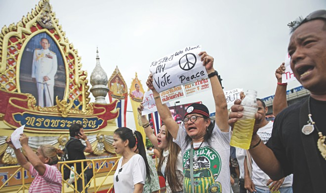 Anti-coup protesters shout slogans during a rally at Victory monument in Bangkok yesterday.