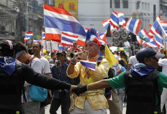 An anti-government protester blows a trumpet during a rally in central Bangkok March 28, 2014.  Photo: AP