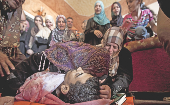 The mother and sister of Palestinian Mahmud al-Sewati mourn over his body during his funeral in Gaza City, yesterday. Photo:AFP