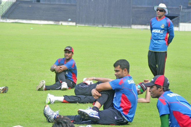 Bangladesh cricketers stretch during their last practice session before Eid ahead of the West Indies tour as coach Chandika Hathurusingha (R) looks on at the Sher-e-Bangla National Stadium in Mirpur yesterday. PHOTO: STAR