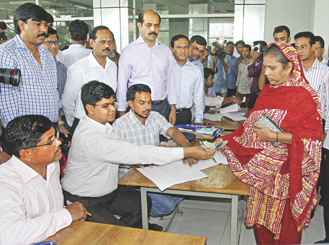 A worker of Tuba Group receives partial payments of their dues at Bangladesh Garment Manufacturers and Exporters Association's office in Dhaka yesterday. Photo: Bangla Chokh