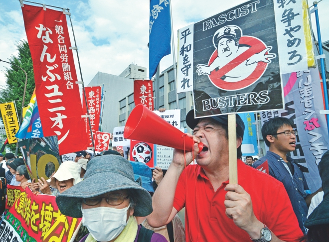 Protestors hold placards and shout anti Abe government slogans during a rally in front of the prime minister's official residence in Tokyo, yesterday. Photo: AFP