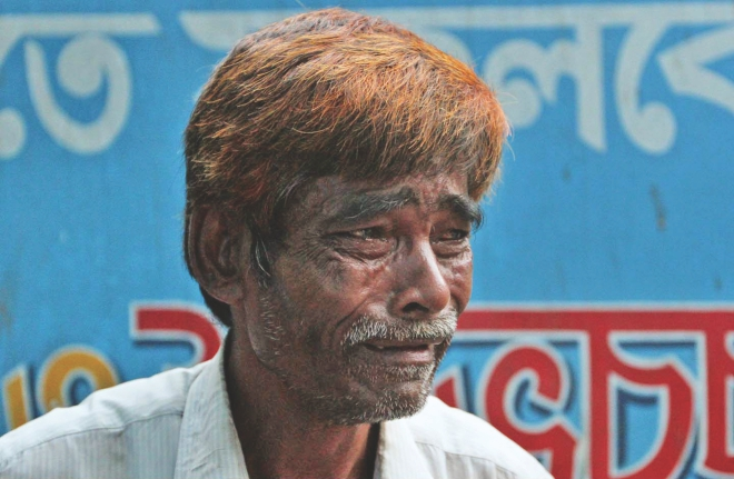 Jashim's father in tears at a clinic in Chittagong yesterday after seeing his son's body. Jashim, a worker at a ship-breaking yard in Sitakunda, was killed in an accident inside a ship along with three fellow workers.  Photo: Anurup Kanti Das
