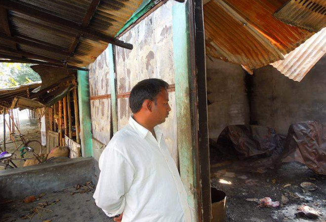 Trader Binod Kumar Roy gives a bleak look at his warehouse torched by Jamaat-Shibir men at Beltoli Bazar in Nilphamari district on the night of December 12 last year in reaction to the execution of Jamaat leader Abdul Quader Mollah. Photo: Star
