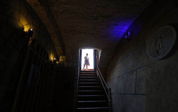 A girl stands in the entrance to the cellar where the company TRAP operates two escape room games in Budapest August 1, 2014. Photo: Reuters