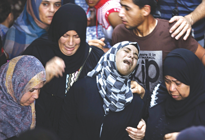 Relatives of Hasan Baker, a 60-years-old Palestinian, grieve during his funeral in Gaza City yesterday. A series of Israeli air strikes earlier killed seven people in Gaza, including five members of the same family. Photo: AFP